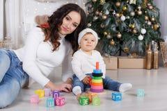 Maman avec une petite fille jouant le réveillon de Noël sur le fond d'un bel arbre de Noël Images stock