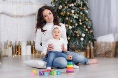 Maman avec une petite fille jouant le réveillon de Noël sur le fond d'un bel arbre de Noël Image libre de droits
