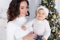 Maman avec une petite fille jouant le réveillon de Noël sur le fond d'un bel arbre de Noël Photographie stock libre de droits