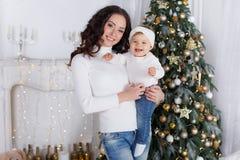 Maman avec une petite fille jouant le réveillon de Noël sur le fond d'un bel arbre de Noël Photos libres de droits