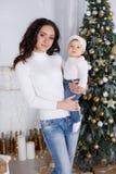 Maman avec une petite fille jouant le réveillon de Noël sur le fond d'un bel arbre de Noël Images libres de droits