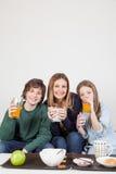 Maman avec vos deux fils buvant du jus dans le petit déjeuner Photographie stock libre de droits