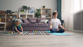Maman détendant en position de lotus tandis qu'enfant calme jouant avec les blocs en bois de jouets banque de vidéos