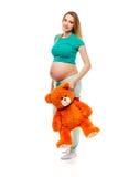 Maman dans la grossesse tenant un ours de nounours La femme enceinte tenant le nounours concernent son ventre, sur le fond blanc Image libre de droits