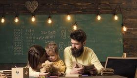 Maman de écoute de garçon avec l'attention Concept de Homeschooling Le père enseigne le fils, livre de lecture, alors que jeu de  photographie stock