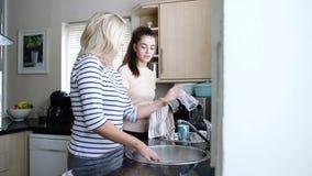 Maman de aide avec des plats banque de vidéos
