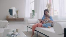 Maman de famille et fils heureux d'enfant utilisant le comprimé numérique se reposant sur le sofa, mère de sourire de parent avec clips vidéos