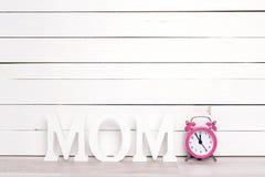 MAMAN de lettres avec le réveil rose sur le fond en bois blanc Photographie stock