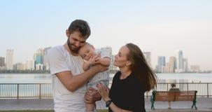Maman de papa de parents de ville soulever sa position de fils sur le bord de mer à l'arrière-plan de la ville clips vidéos