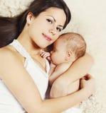 Maman de portrait de plan rapproché jeune dormant avec le bébé à la maison Image stock