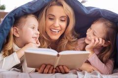 Maman de sourire lisant un livre pour ses filles Photos libres de droits