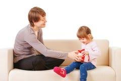 Maman donnant un cadeau à sa petite fille. D'isolement Photo stock