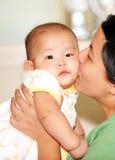 Maman embrassant la chéri Photographie stock libre de droits