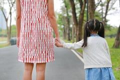 Maman en gros plan et fille tenant des mains dans le jardin ext?rieur de nature Vue arri?re image libre de droits