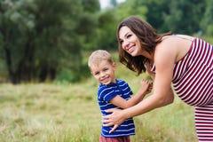 Maman enceinte heureuse et son fils Photographie stock libre de droits