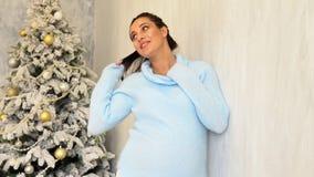 Maman enceinte heureuse par l'arbre de Noël avec des cadeaux de Noël banque de vidéos