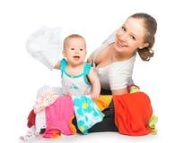 Maman et bébé avec la valise et les vêtements prêts pour le déplacement Image libre de droits