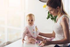 Maman et bébé dans la cuisine La femme va alimenter le bébé avec l'aliment pour bébé Images stock
