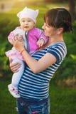 Maman et bébé heureux en parc vert Image stock