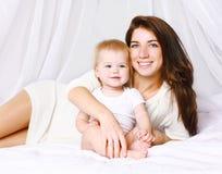 Maman et bébé heureux sur le lit Images libres de droits
