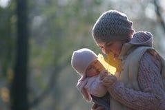 Maman et bébé regardant la feuille d'érable jaune photographie stock
