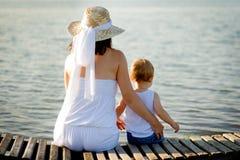 Maman et bébé se reposant sur la banque près de l'eau Photographie stock