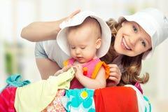 Maman et bébé avec la valise et les vêtements prêts pour le déplacement Photo stock