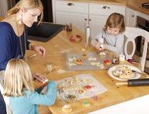 Maman et deux descendants faisant cuire des biscuits Image stock