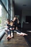 Maman et deux filles ensemble à la fenêtre Photographie stock libre de droits