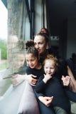 Maman et deux filles ensemble à la fenêtre Images libres de droits