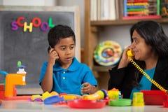 Maman et enfant dans l'arrangement à la maison d'école Photos stock