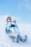 Maman et enfant en bas âge glissant en bas de la côte Images stock