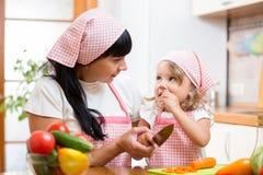 Maman et enfant préparant la nourriture saine à la cuisine Images stock