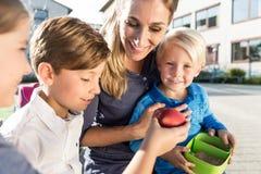 Maman et enfants prenant le déjeuner veggie avec des rayures de paprika Photo stock