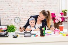 Maman et femme d'affaires travaillant avec l'ordinateur portable à la maison et jouant avec son bébé Image libre de droits