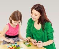 Maman et fille à la table jouant les jeux éducatifs Photographie stock