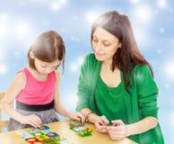 Maman et fille à la table jouant les jeux éducatifs Photographie stock libre de droits