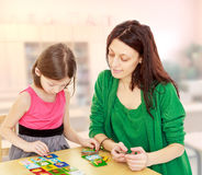 Maman et fille à la table jouant les jeux éducatifs Photos libres de droits