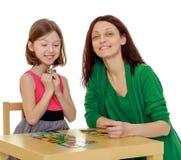 Maman et fille à la table jouant les jeux éducatifs Images stock
