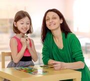 Maman et fille à la table jouant les jeux éducatifs Photo stock