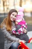 Maman et fille caressant sur un banc de parc Images libres de droits
