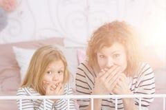 Maman et fille couvrant leurs bouches Image stock