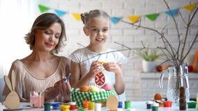 Maman et fille décorant des branches avec les jouets fabriqués à la main, traditions de Pâques images libres de droits