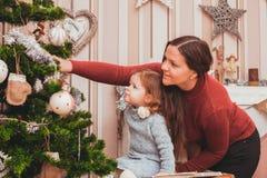 Maman et fille décorant l'arbre de Noël Photos stock