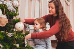 Maman et fille décorant l'arbre de Noël Photo libre de droits