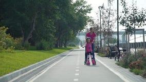 Maman et fille dans des patins de rouleau banque de vidéos
