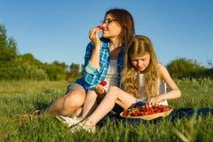 Maman et fille dans la nature, les vacances de pays d'été, la mère et l'enfant s'asseyant sur l'herbe mangeant des fraises Photographie stock libre de droits