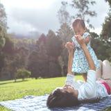 Maman et fille dans les happines s'étendant sur une herbe Photographie stock libre de droits