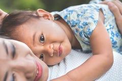 Maman et fille dans les happines s'étendant sur une herbe Photo libre de droits