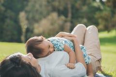Maman et fille dans les happines s'étendant sur une herbe Photos libres de droits